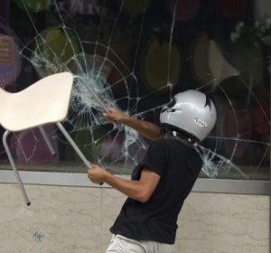Uno de los protestantes rompe la mampara