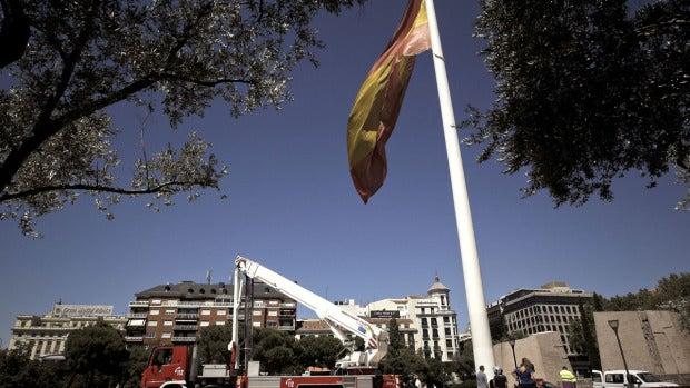 Los bomberos izan de nuevo la bandera de la plaza de Colón