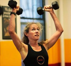 Una mujer hace ejercicio con pesas