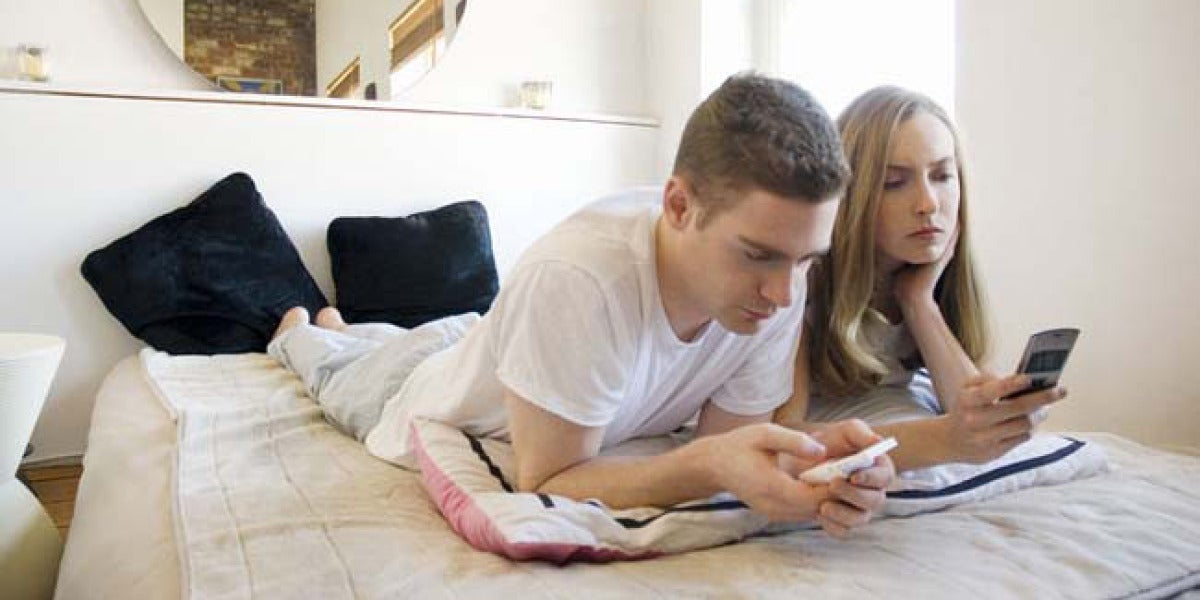 Una pareja utiliza sus móviles en la cama