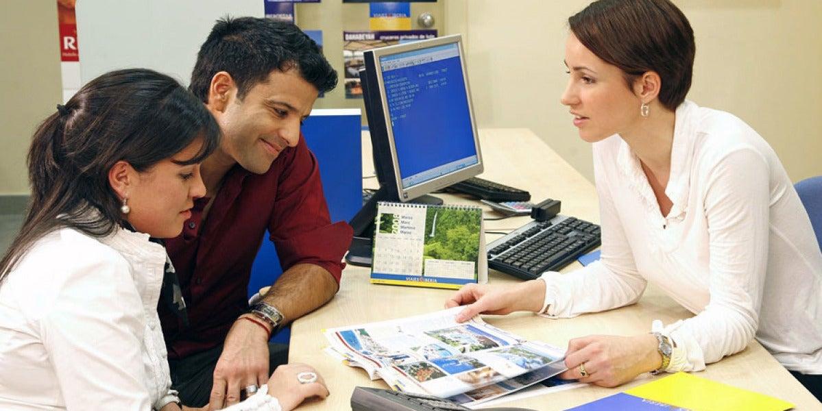 Una pareja reserva sus vacaciones en una agencia de viajes