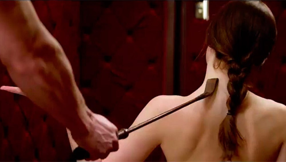 Christian Grey acaricia con una fusta la espalda de Anastasia Steele
