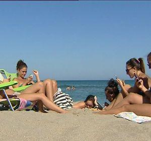 Un grupo de chicas con sus móviles en la playa