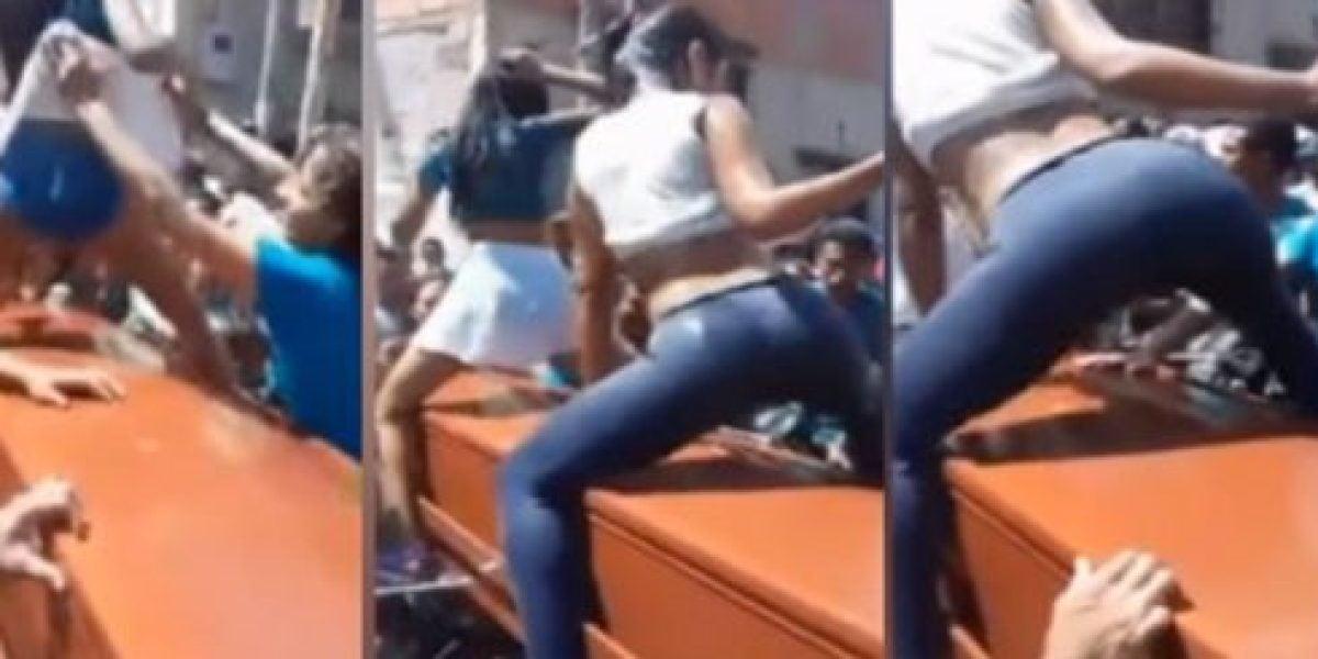 Dos chicas bailando reggaeton sobre un ataúd