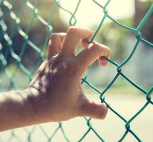 Una mano agarra una valla con rejas