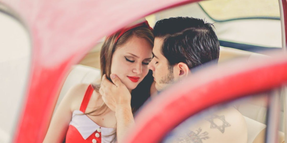 Una pareja se besa en el coche