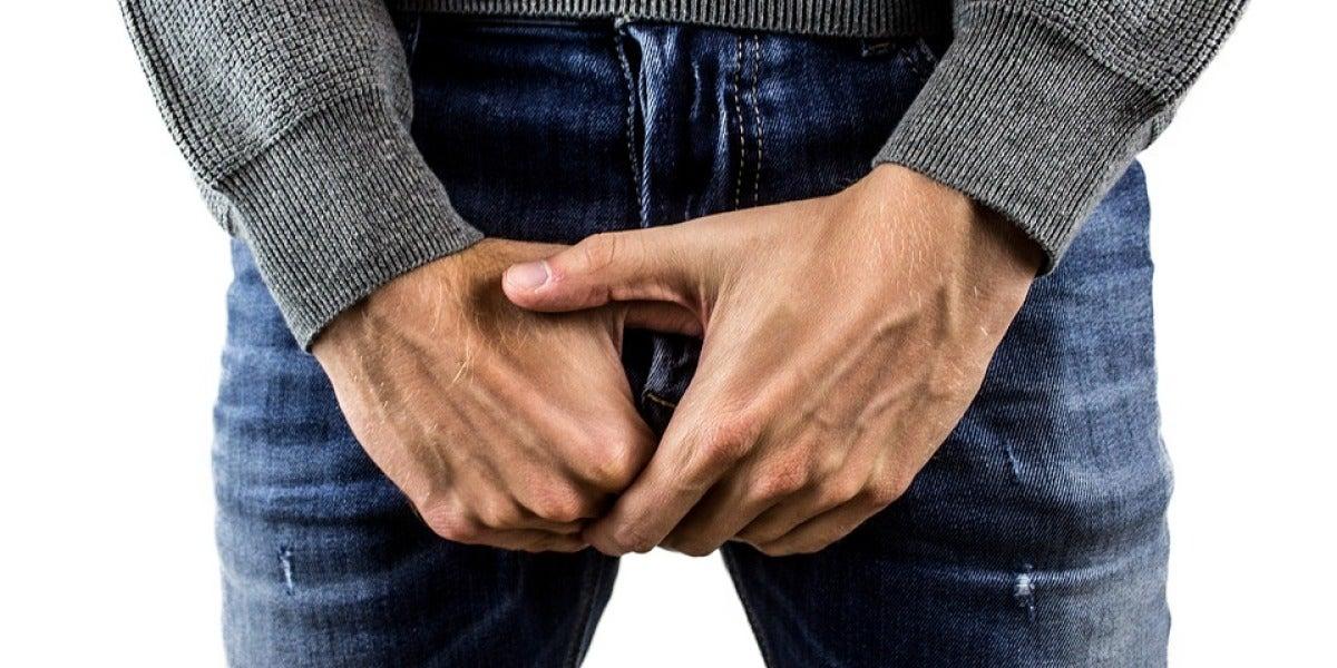 Un hombre se toca los genitales