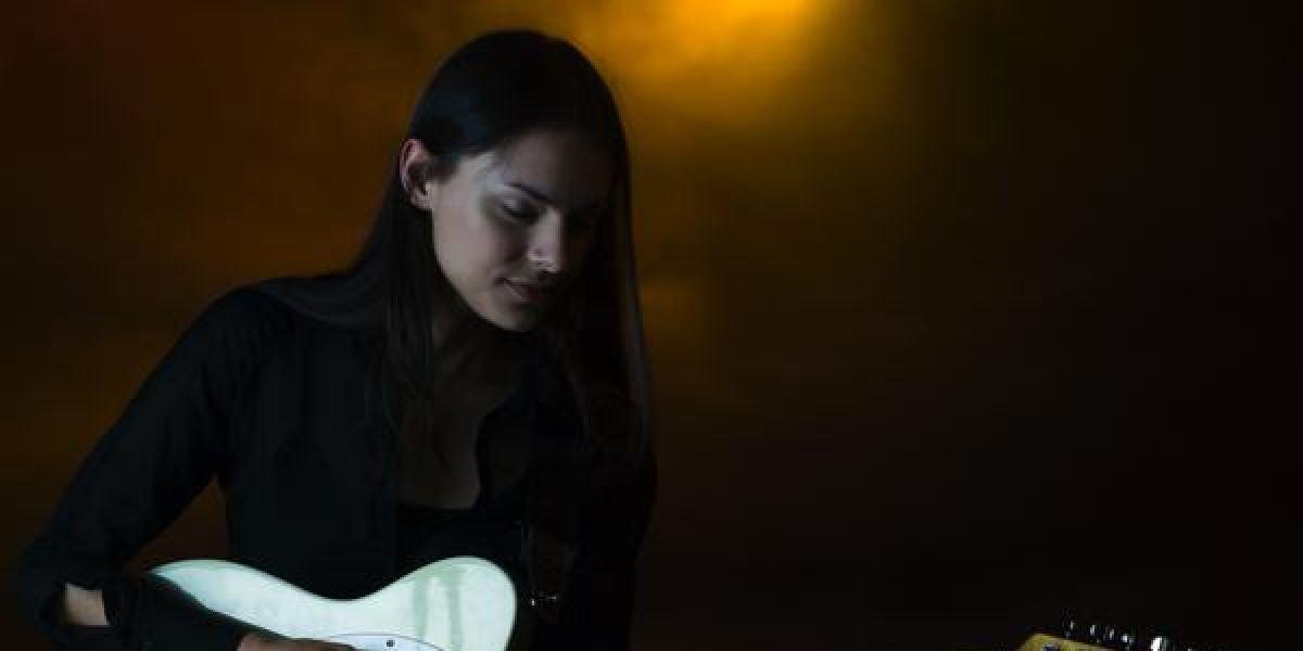 Una chica tocando la guitarra eléctrica en un pub
