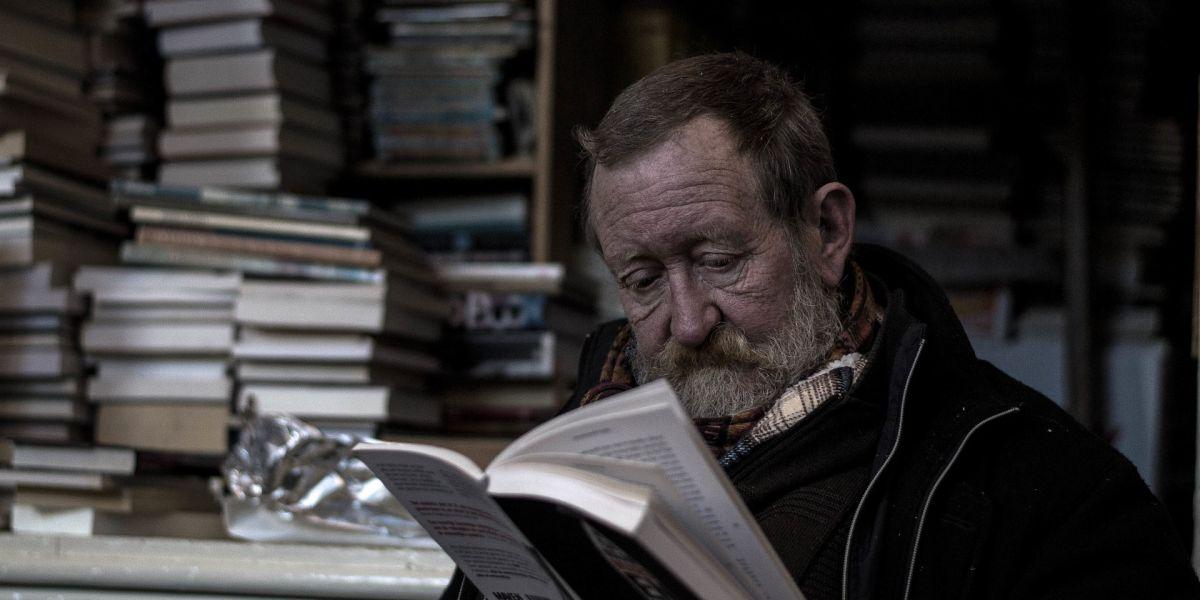 Un hombre leyendo en una biblioteca