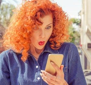 Mujer sorprendida al mirar el móvil
