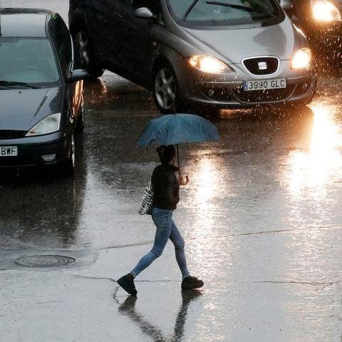 Imagen de una persona que se protege con un paraguas de la lluvia