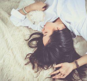 mujer durmiendo en una cama con un perro