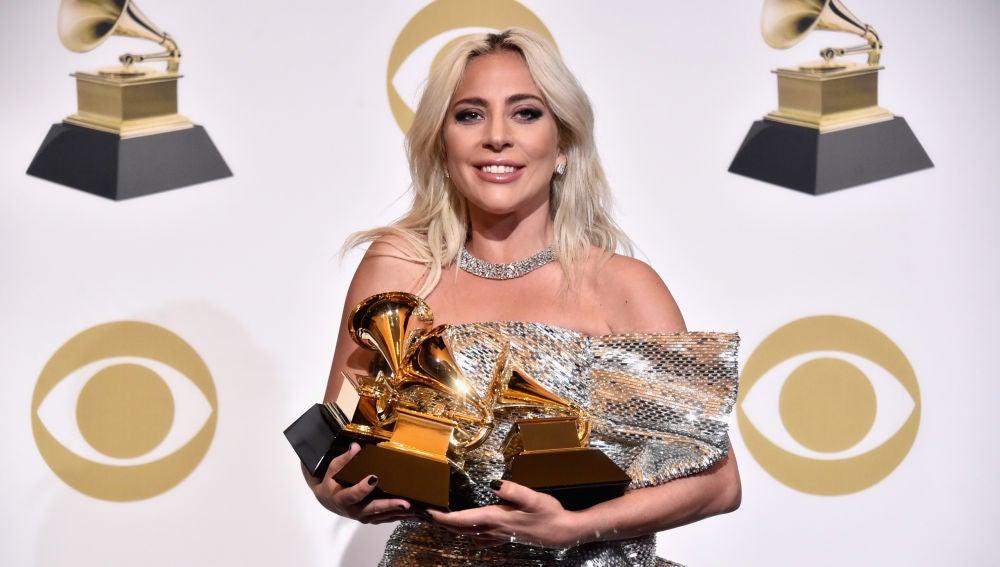 Lady Gaga sujetando sus tres premios Grammy