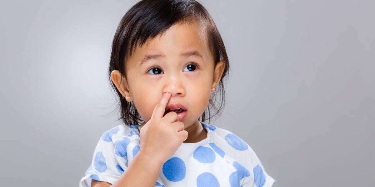 Una niña pequeña metiéndose el dedo en la nariz