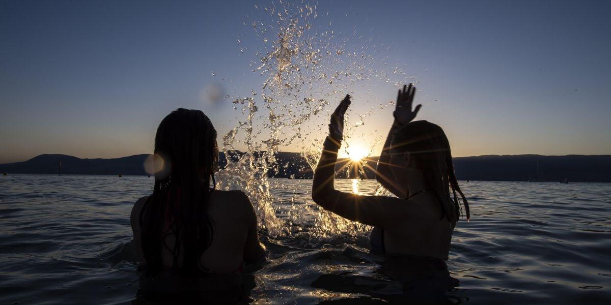 Dos adolescentes disfrutan de la puesta de sol en el agua del Lago de Neuchatel