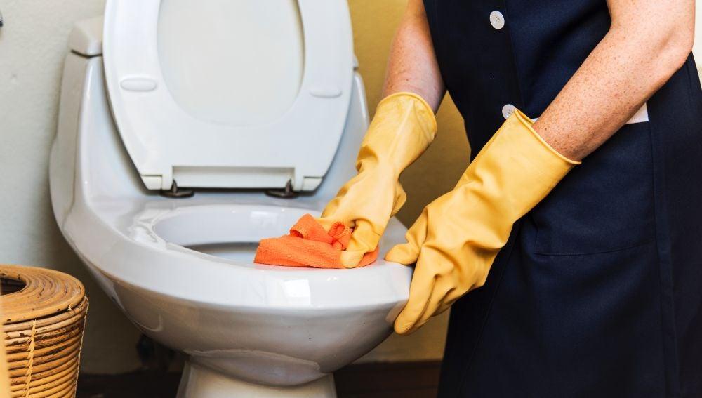 Una persona limpiando un váter