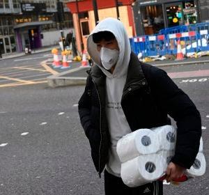 Un ciudadano británico, con rollos de papel higiénico en el brazo izquierdo