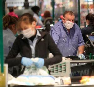 Varias personas hacen la compra en un supermercado de Madrid