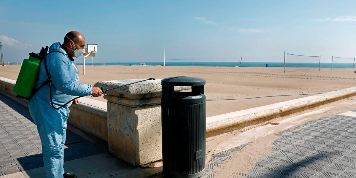 Un operario desinfecta una papelera ante una playa de la Malvarrosa (Valencia)