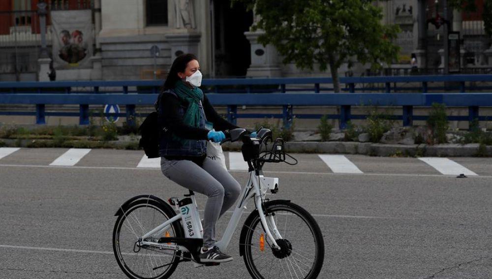 Una mujer con mascarilla y guantes usa una bici de biciMad en Madrid