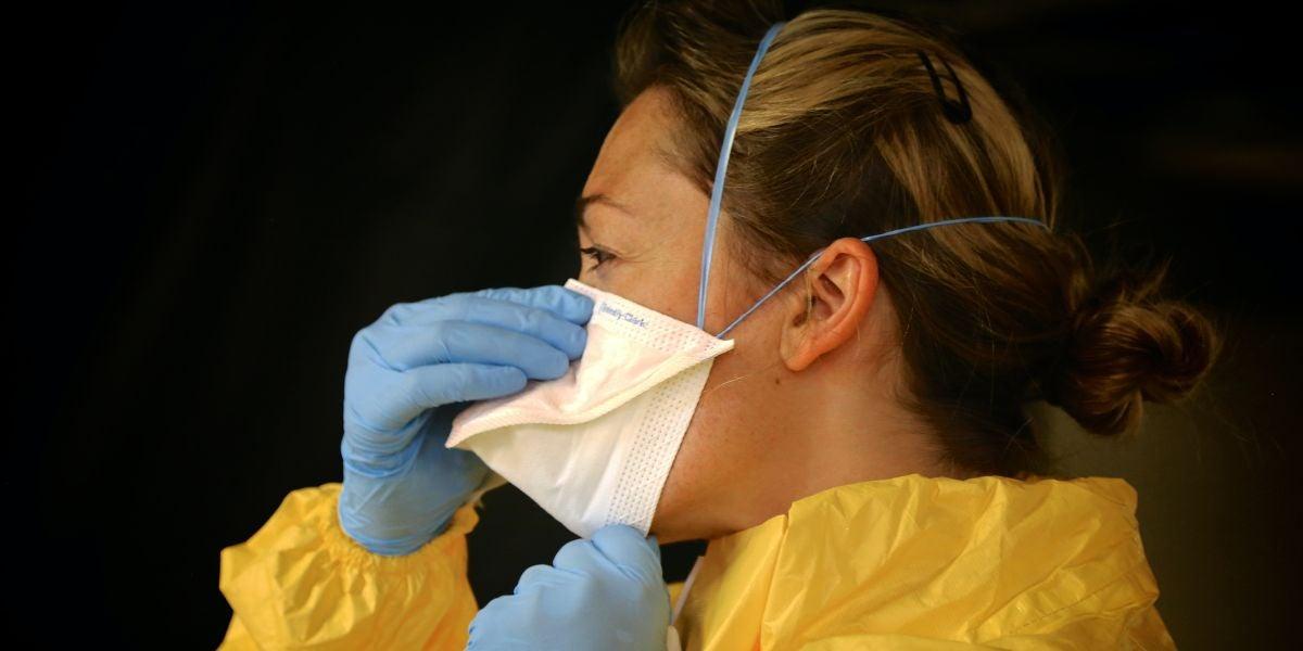 Una enfermera poniéndose la mascarilla