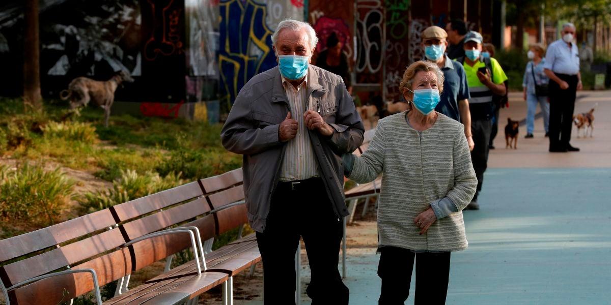 Dos personas mayores paseando con mascarilla