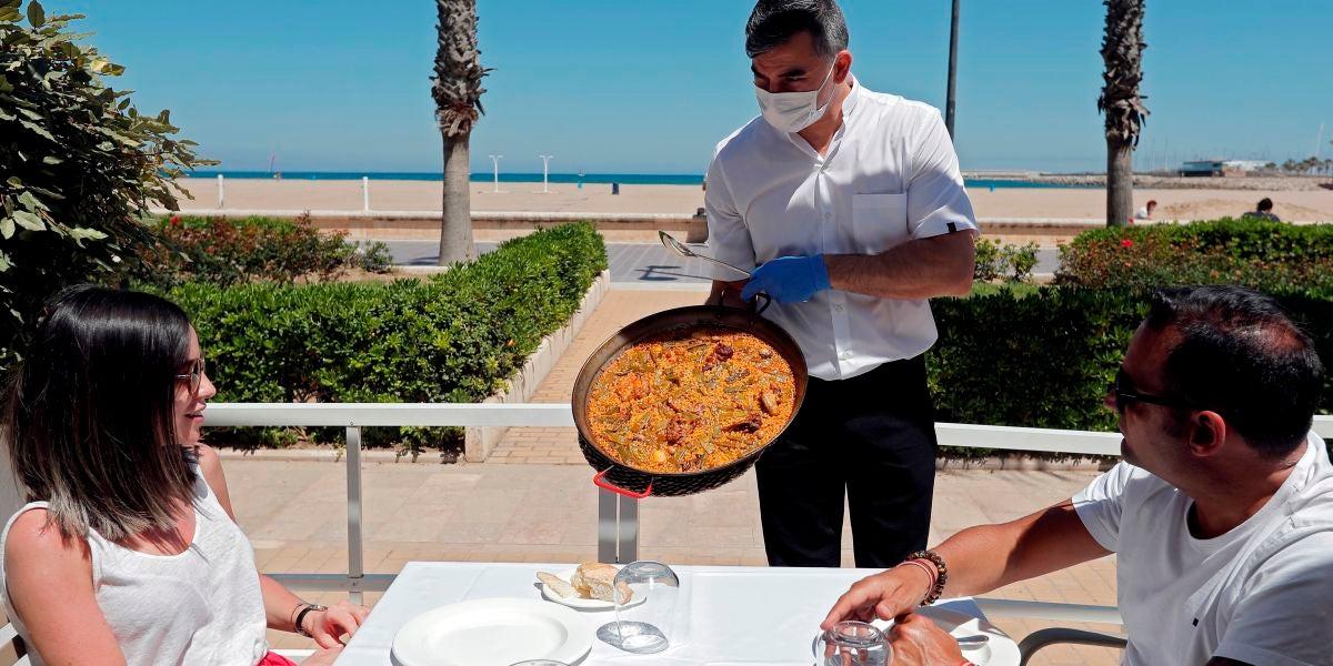 Un camarero sirve una paella en una terraza de un restaurante de la playa de la Malvarrosa de Valencia