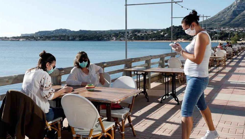 Clientes con mascarillas en una terraza