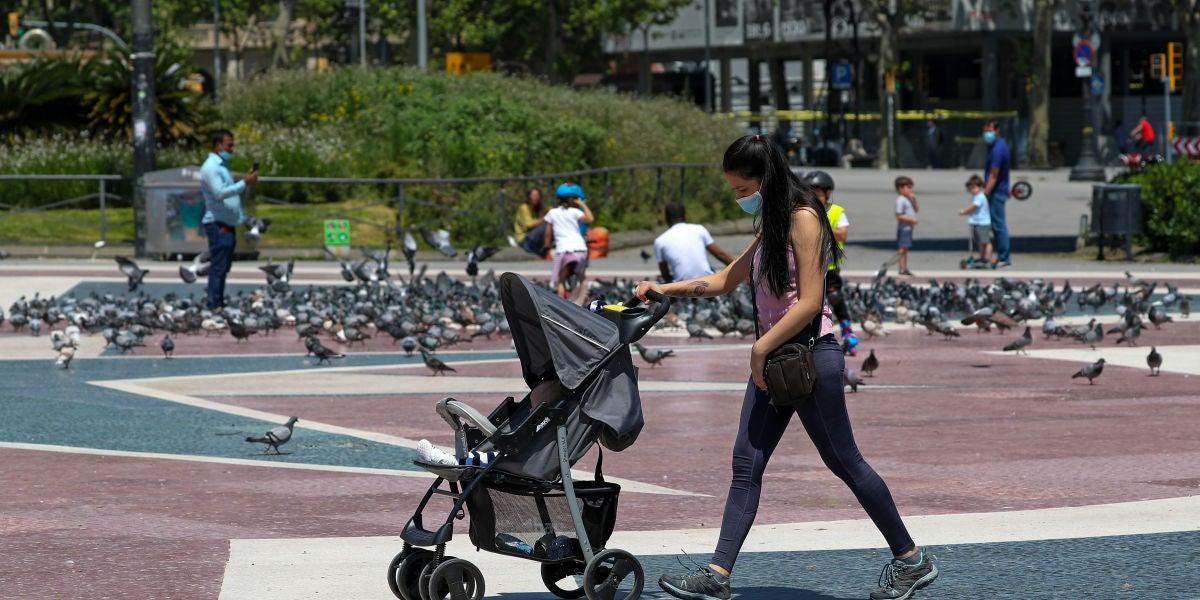 Una mujer con mascarilla empujando un carrito de bebé en Barcelona
