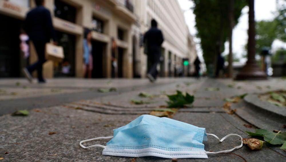 Una mascarilla tirada en el suelo de la calle