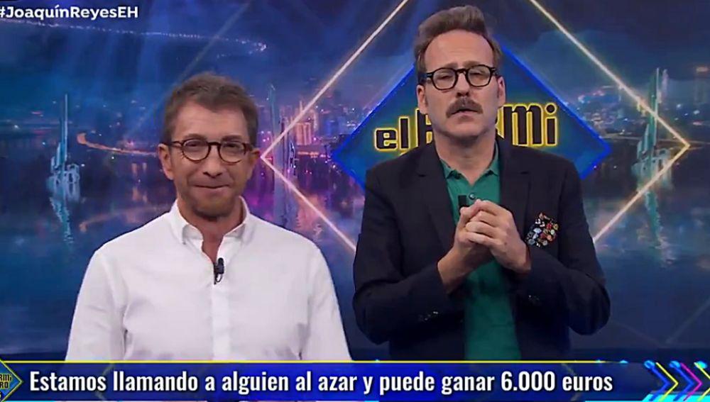 Pablo Motos y Joaquín Reyes intentando repartir la tarjeta de El Hormiguero