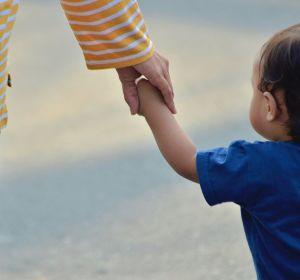 Un niño pequeño pasea de la mano de su madre.