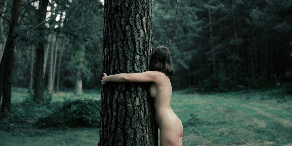 Mujer desnuda abrazando un árbol