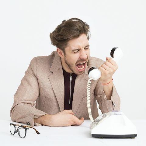 Hombre enfadado gritando al teléfono