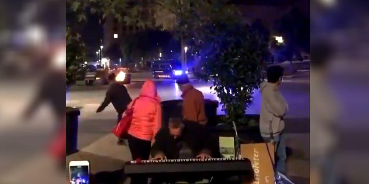 Un hombre toca con los disturbios de fondo en Barcelona
