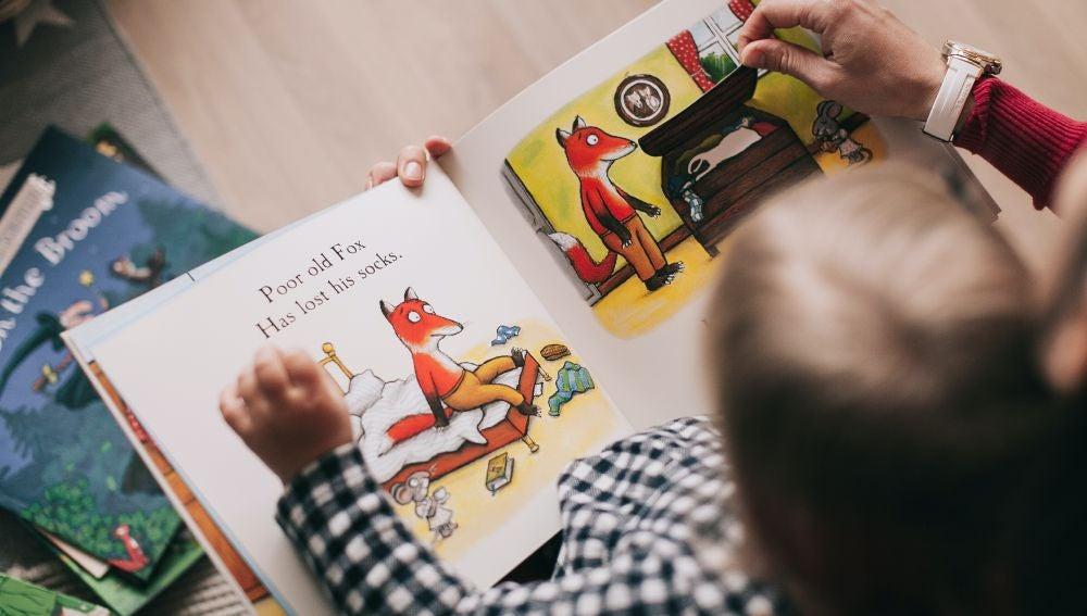 Un niño mirando un libro infantil