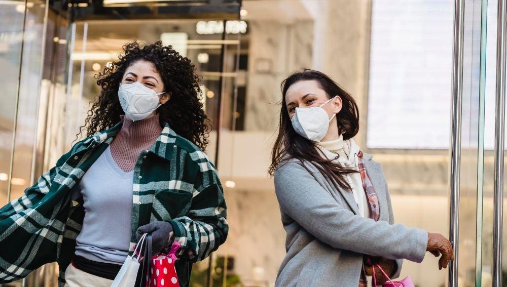 Dos chicas con mascarilla en la calle
