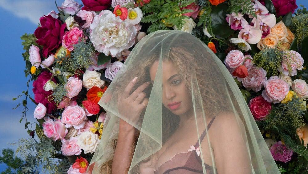 Beyoncé cubierta por un velo y con un fondo de flores