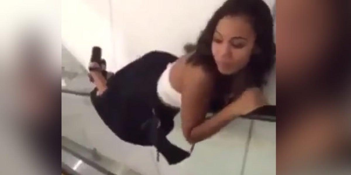 La chica bajando las escaleras mecánicas tumbada en el posamanos