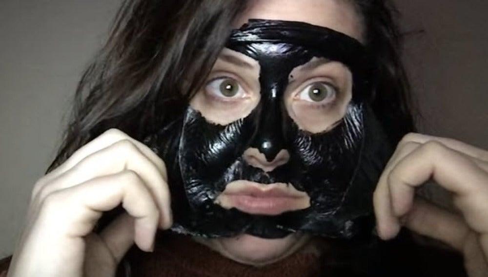 La youtuber intentándose retirar una mascarilla