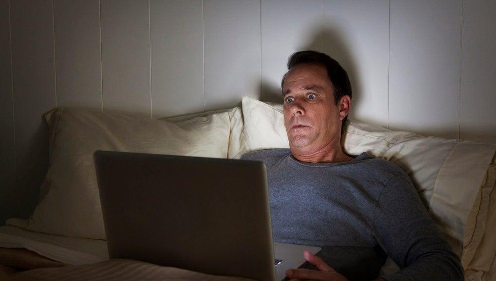 Hombre mirando su portátil sorprendido