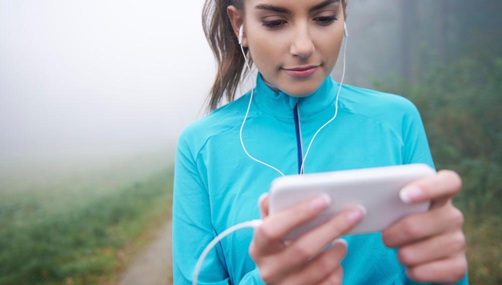 Una runner consulta su aplicación móvil