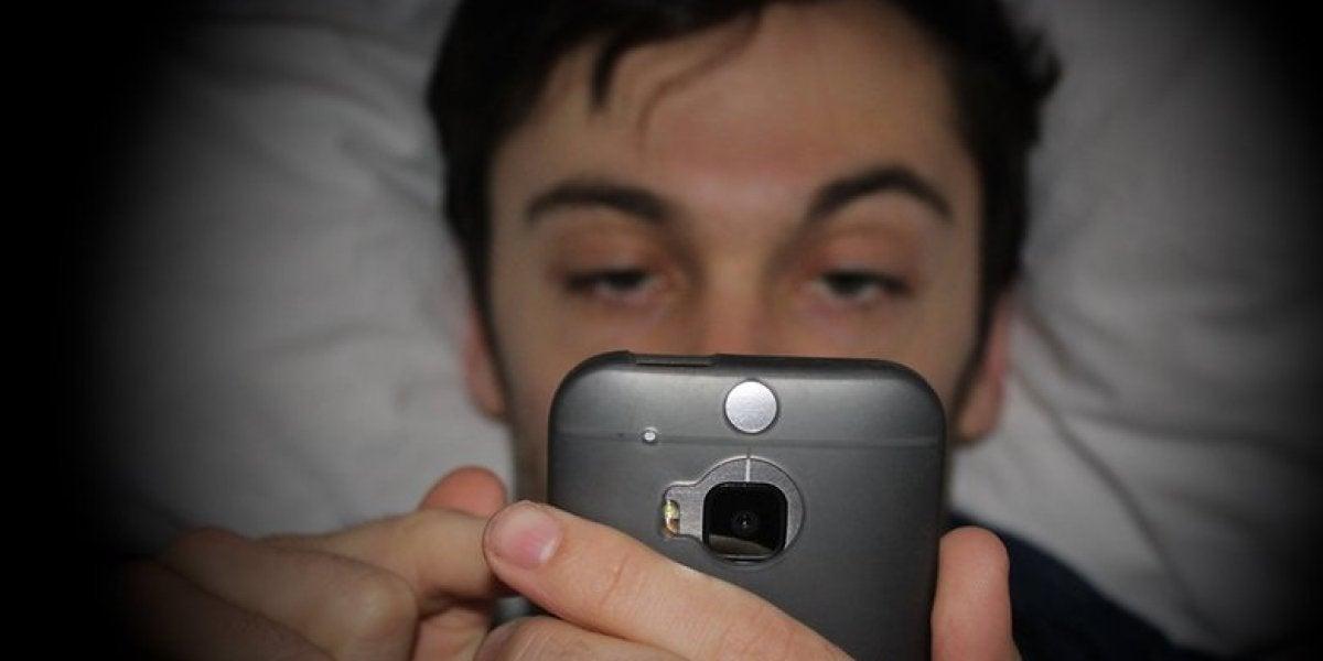 Hombre mirando el móvil en la cama