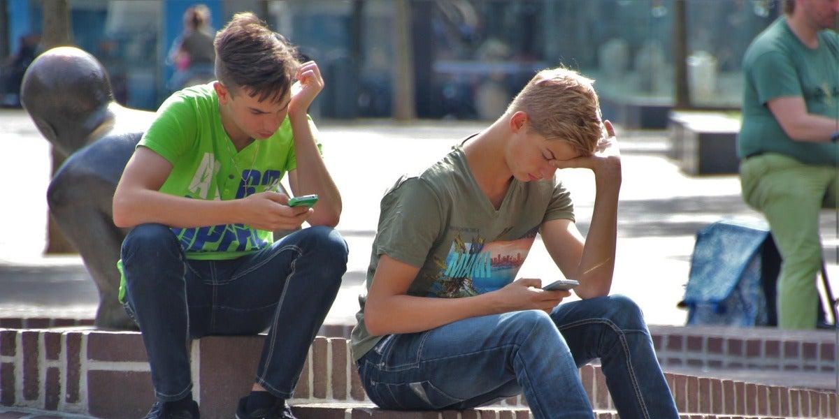 Dos amigosutilizando el móvil