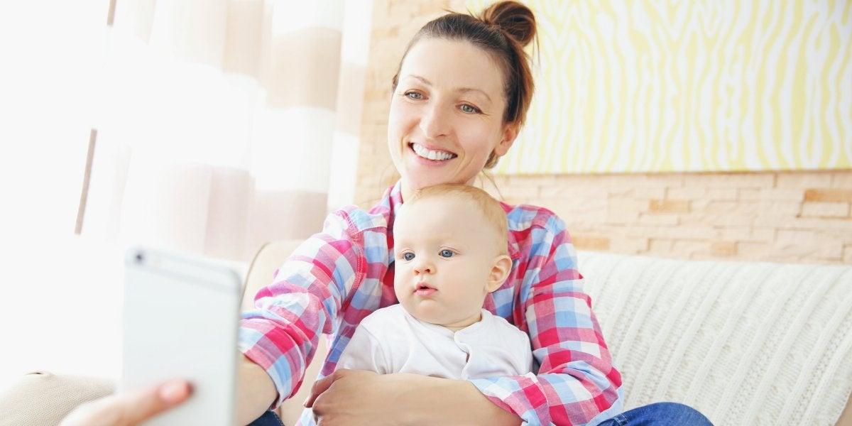 Una mujer haciéndose un selfie con su bebé