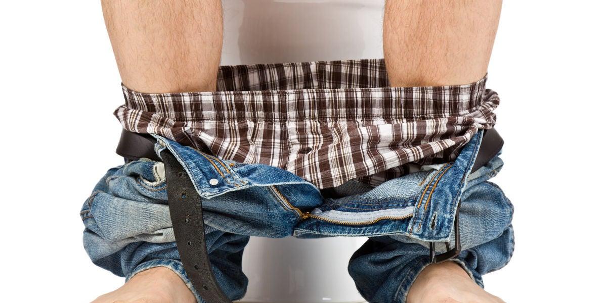 Hombre sentado en el WC