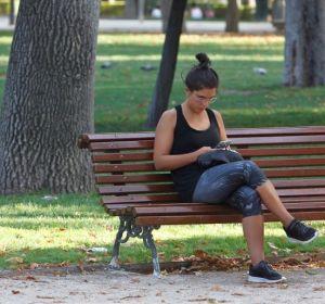 Imagen de archivo de una mujer que consulta su móvil en un banco del madrileño parque del Retiro