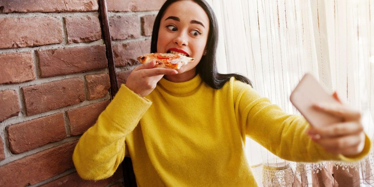 Chica grabándose en Instagram Stories mientras come una pizza