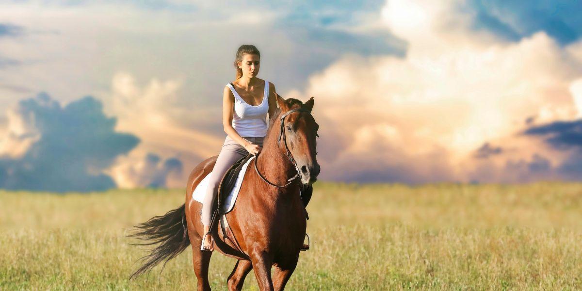 Una mujer montando a caballo