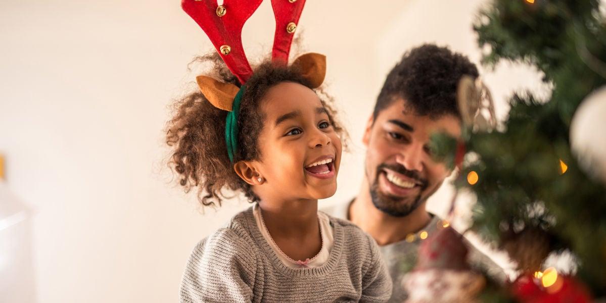 Niña emocionada decorando un árbol de Navidad